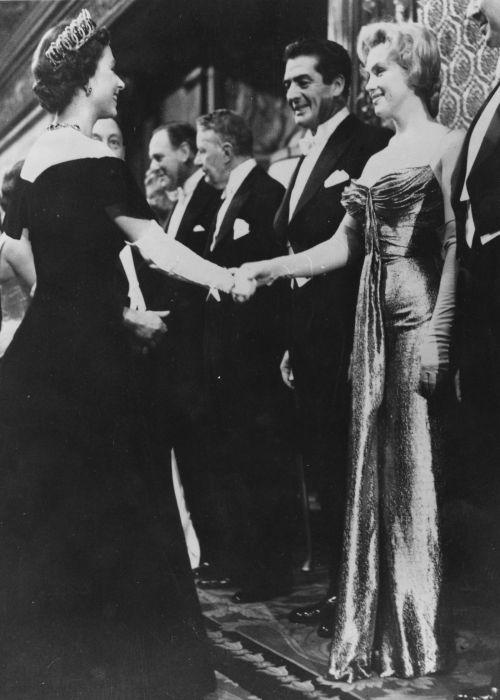 Знаменитая американская певица и киноактриса Мэрилин Монро на встрече с королевой Великобритании в 1956 году.