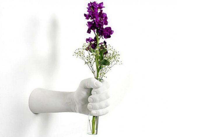 Неординарная ваза в форме руки, которая дарит цветы.