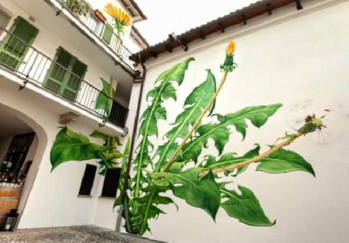Огромный рисунок одуванчика на стене дома.
