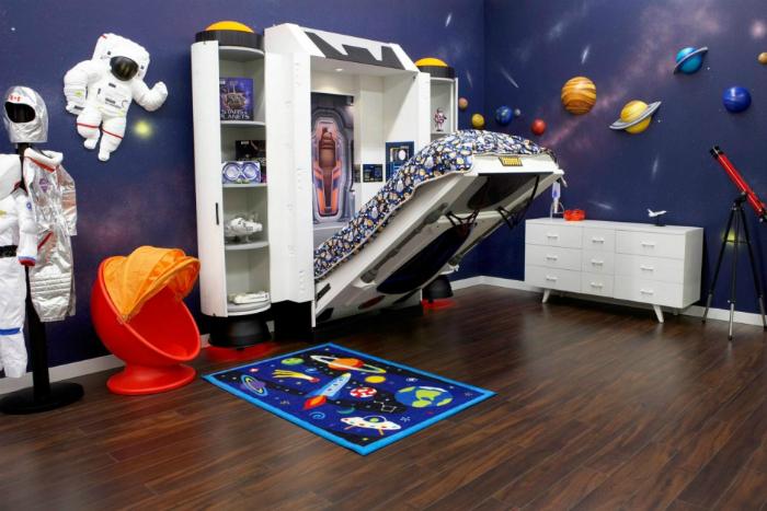 Детская с изображениями планет на стенах, телескопом и оригинальной мебелью.