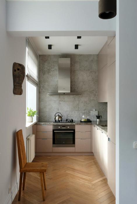 Кухня с акцентной стеной, стилизованной под бетон.