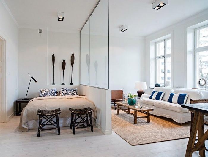 Спальня, отделенная от гостиной стеклянной стеной.