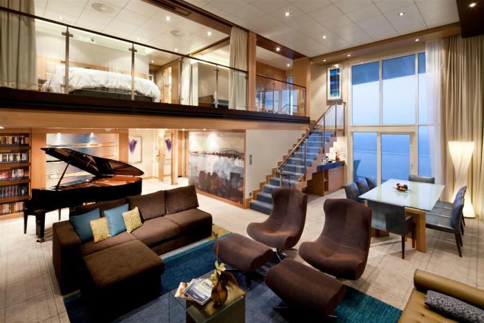 Светлая двухярусная комната с комфортабельной мебелью и черным роялем.