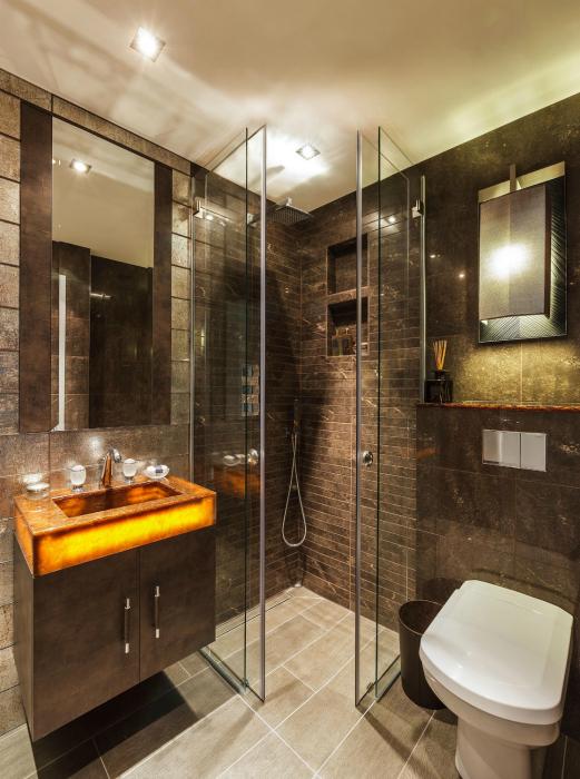 Современная душевая кабинка с коричневыми стенами.