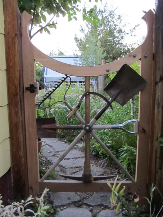 Деревянная калитка, декорированная старым садовым инструментом.