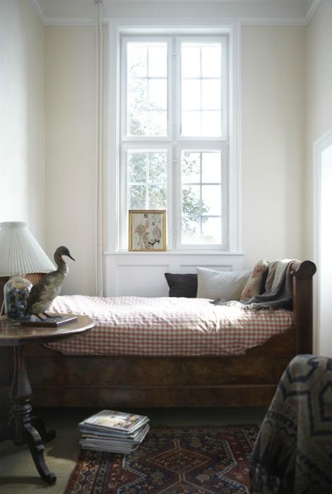Маленькая спальня с большим окном.