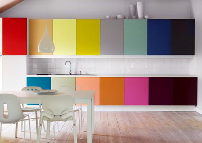 Белая кухня с разноцветными шкафчиками.