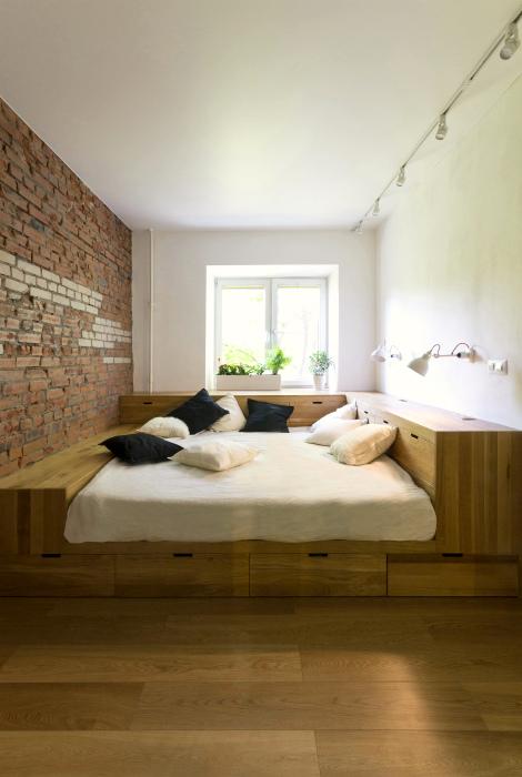 Кровать, окруженная шкафчиками.