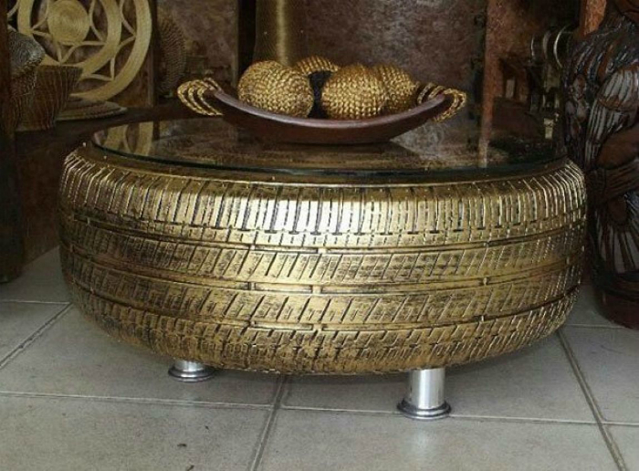 Кофейный столик из старой автомобильной покрышки золотого цвета и круглого стекла.