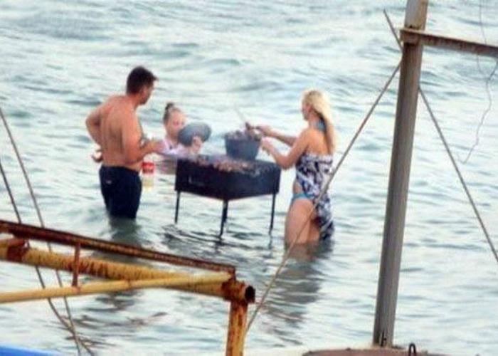 Веселые ребята жарят шашлык прямо в реке.