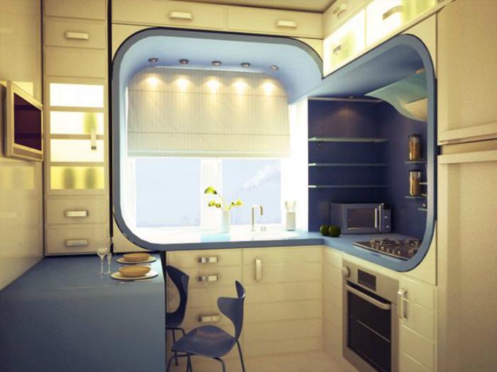 Крохотная кухня с большой рабочей поверхностью, которая также выполняет функции стола, и необычным дизайном окна.