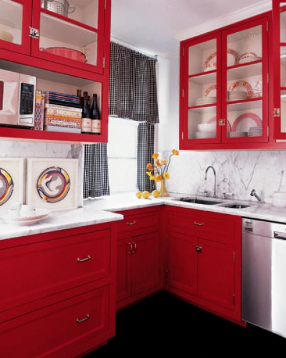 Угловая кухня с красными шкафчиками.