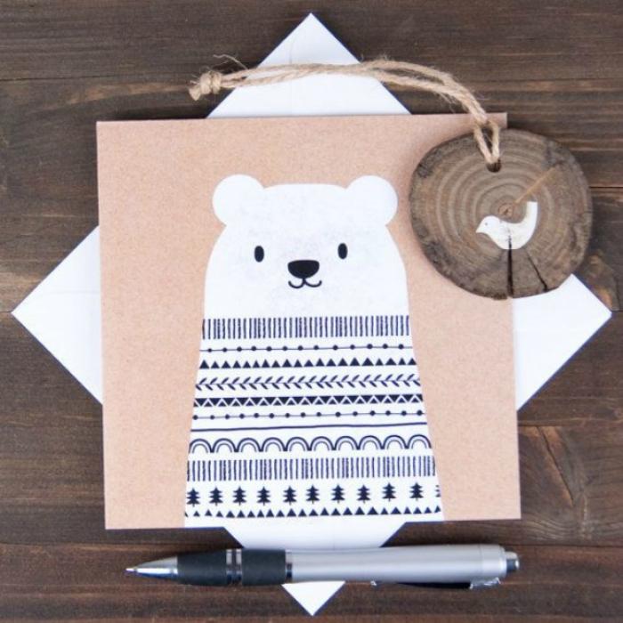 Фигурку мишки нужно вырезать из обычной белой бумаги, а потом ручкой нарисовать ему свитер с узорами.