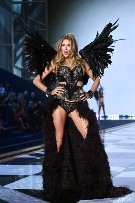 Даутцен Крез в черном кружевном корсета с огромными черными крыльями за спиной.