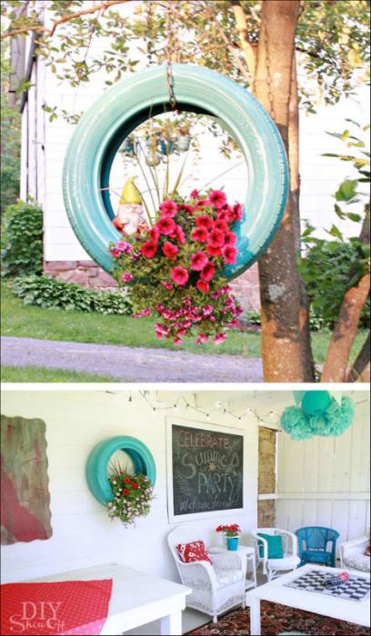 Кашпо для цветов в старой шине, прибитой к стене.