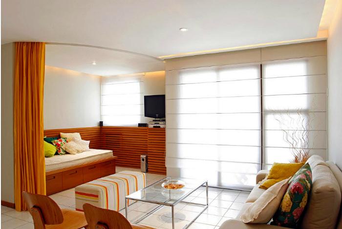 Бело-оранжевая комната, зонированая шторкой.