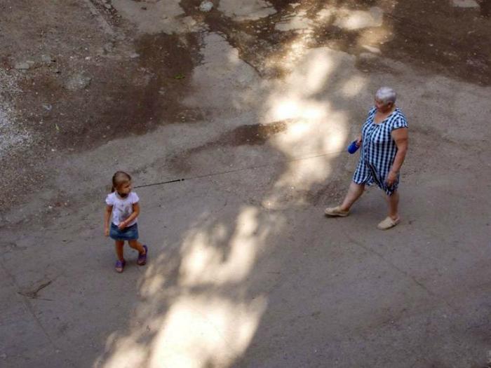 Заботливая бабушка выгуливает внучку на поводке, чтоб не убежала.