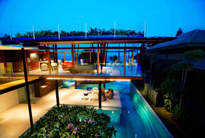 Дом из деревянных балок и стекла с необычным бассейном.
