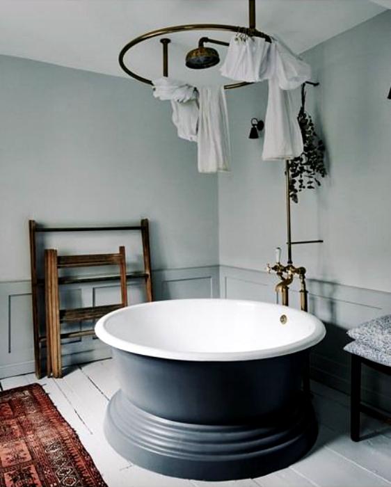 Светлый санузел с оригинальной круглой ванной.