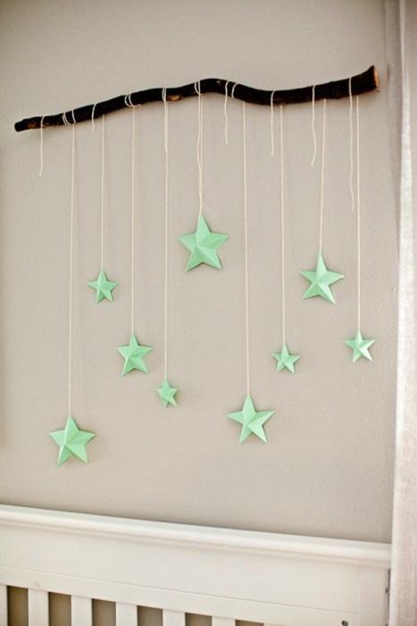 Красивая композиция из дерева и подвесок-звездочек, которая прекрасно впишется в интерьер детской-комнаты.