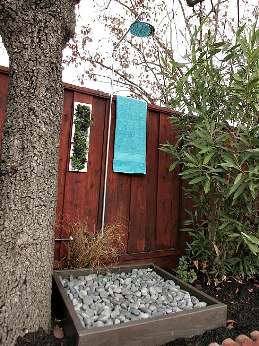 Летний душ с деревянным поддоном, заполненным галькой.
