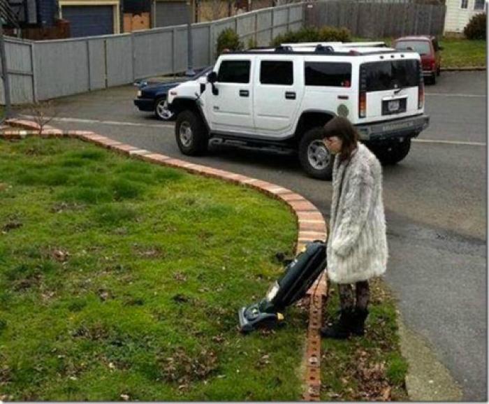 Женщина вышла пропылесосить газон.