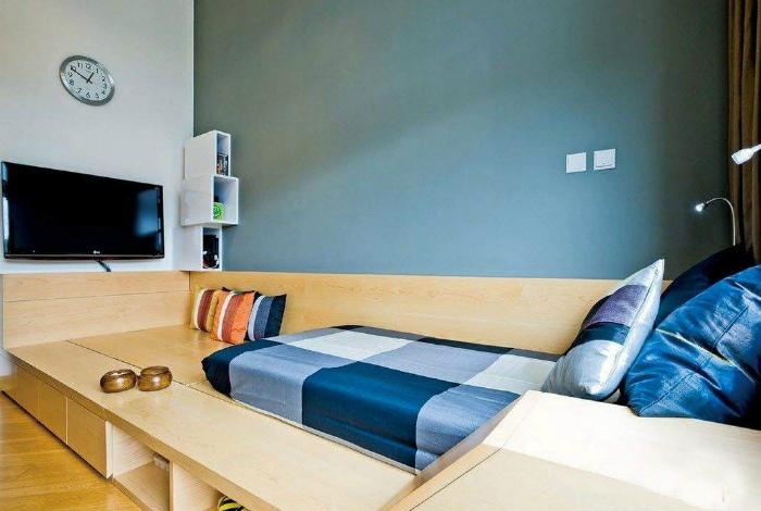 Спальная зона на невысоком подиуме из светлого дерева.