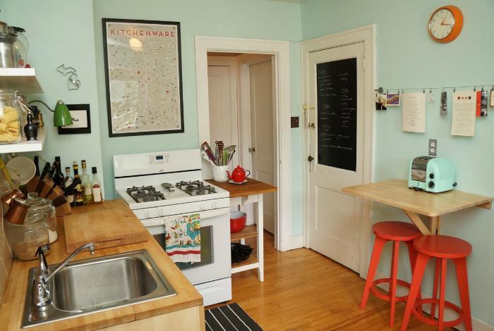 Маленькая кухня, выполненная в стильном мятном цвете, обставленная компактной деревянной мебелью.