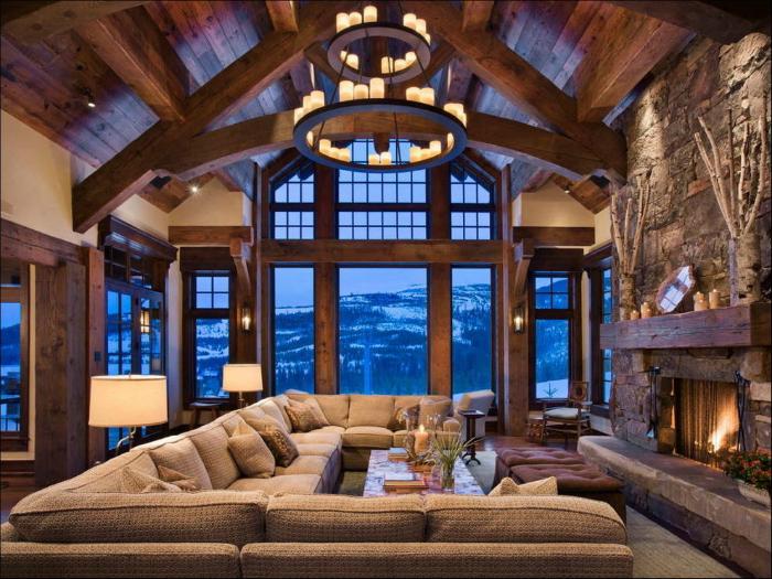 Уютная комната, отделанная серым камнем с огромным диваном и камином.