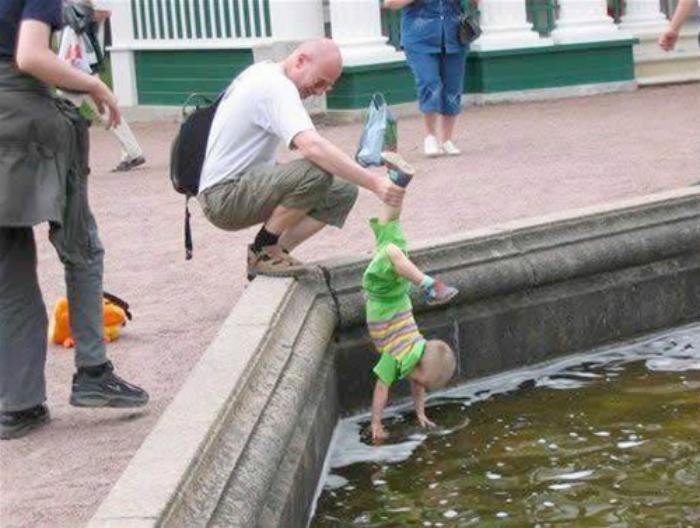 Заботливый отец помогает малышу собирать монетки из фонтана.