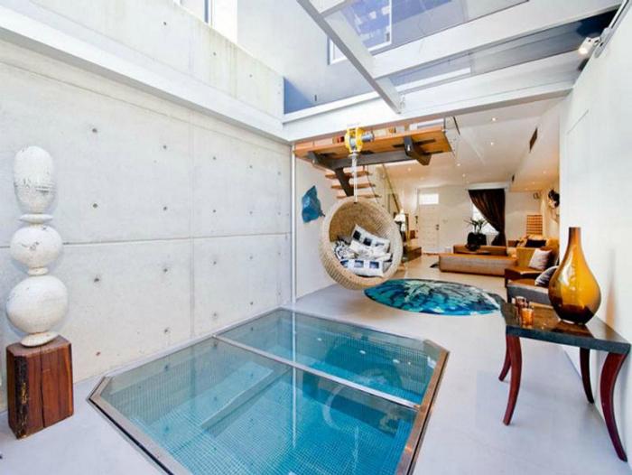 Белоснежная комната с небольшим закрывающимся бассейном и плетеным висящим креслом.