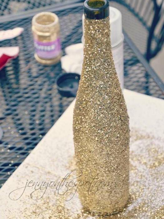 Покройте винную бутылку клеем и обсыпьте сверху блестками.