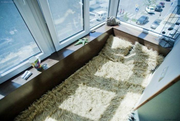 Огромные окна и матрас, застеленный пушистым покрывалом для комфортабельного отдыха на свежем воздухе.