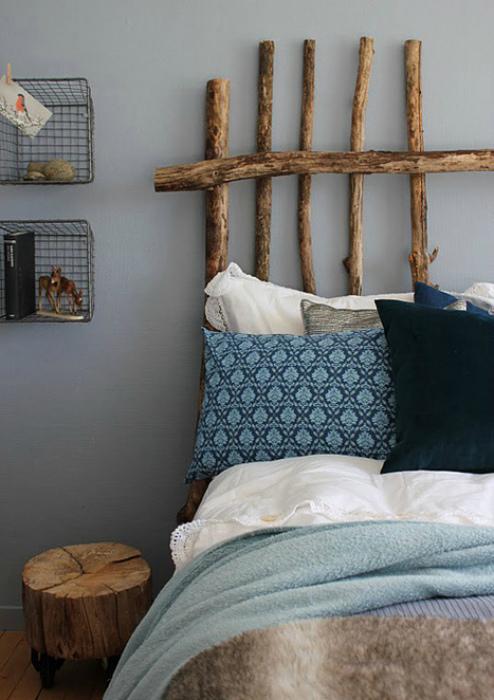 Изголовье кровати, сделанное из тонких сухих стволов.