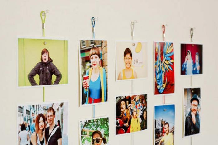 Фотографии, развешанные на яркие магнитные шнурочки или на магнитную стену.