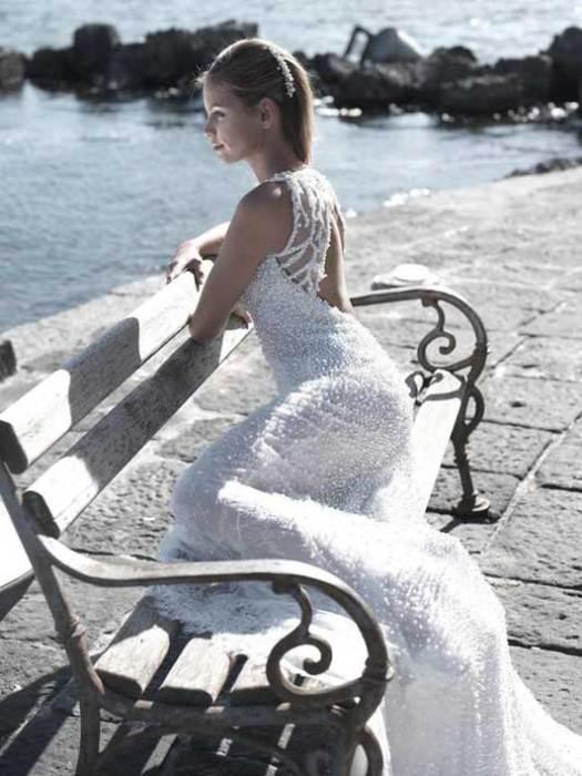 Шелковое кружевное платье со шлейфом выполнено по моде 30-х годов и декорировано натуральным жемчугом, бриллиантами и хрусталем.