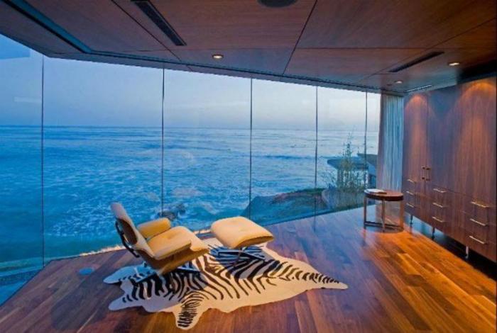 Комната с огромными панорамными окнами и минимумом мебели.