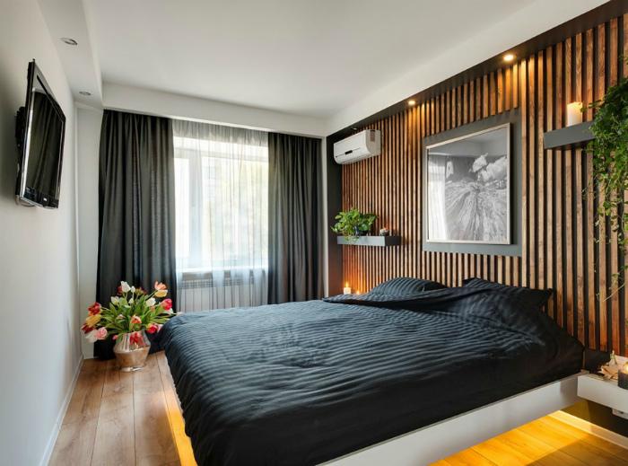 Стильная спальня с деревянной акцентной стеной.