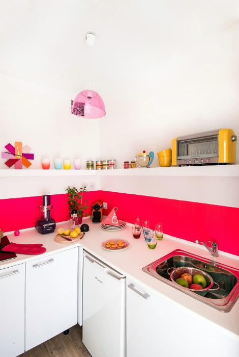 Небольшая белая кухня с ярким фартуком.