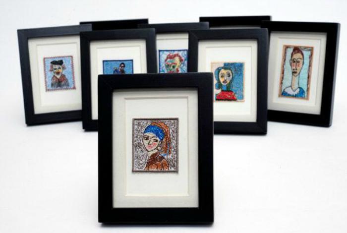 Коллекция миниатюрных копий шедевров живописи в рамках.