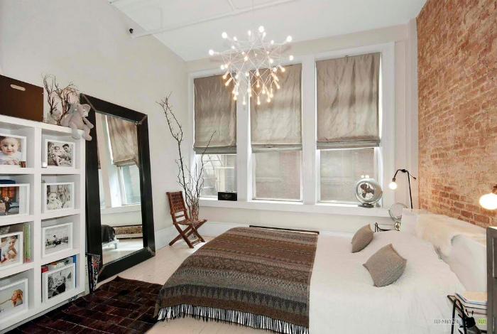 Уютная спальня с кирпичной стеной.