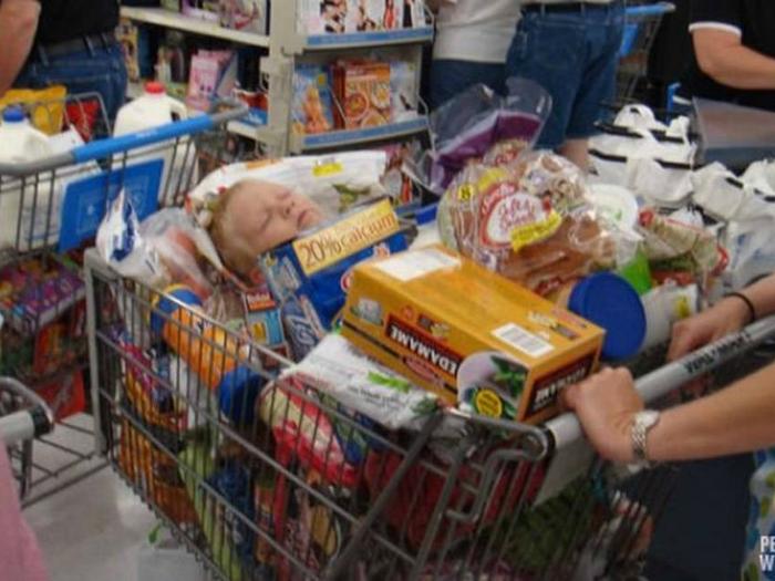 Несчастный ребенок так устал от хождения по магазину, что уснул прямо в тележке с продуктами.