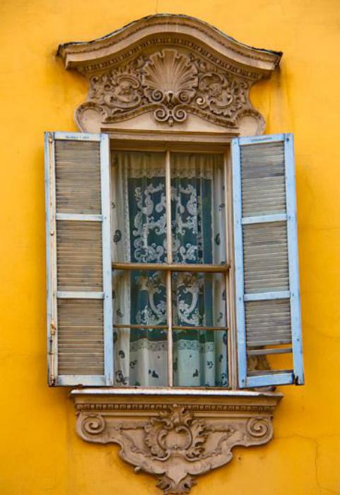 Окно в раме, стилизованной под золото, украшенное лепниной. Парма, Италия.