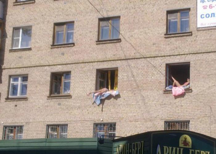 В солнечные деньки русские девушки загорают на подоконниках.