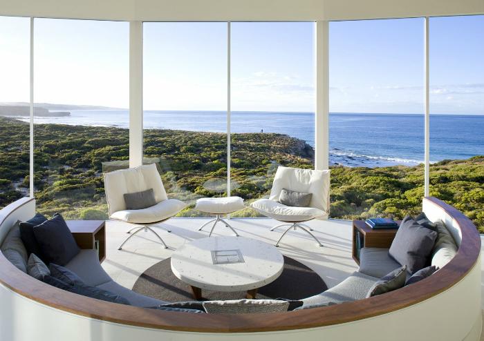 Гостиная с прозрачными стенами и большим круглым диваном.