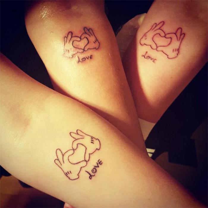 Татуировки с изображением рук, сложенных в сердце на руках у мамы и ее дочерей.