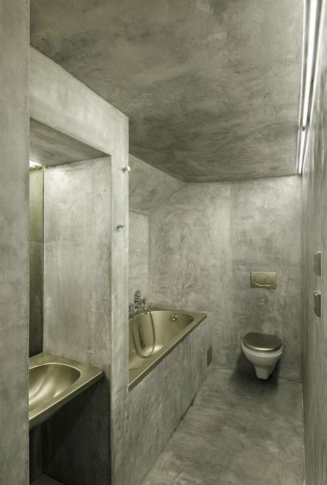 Узкая ванная комната с серыми стенами.