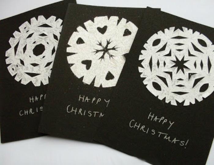 Открытка с белоснежными фигурными снежинками из бумаги на черном фоне.