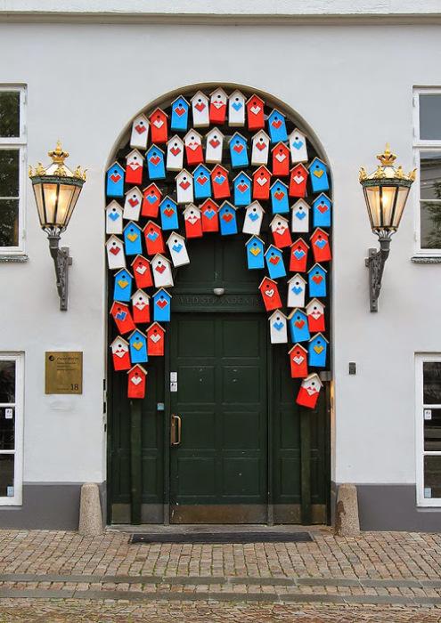 Дверь, украшенная множеством ярких скворечников.