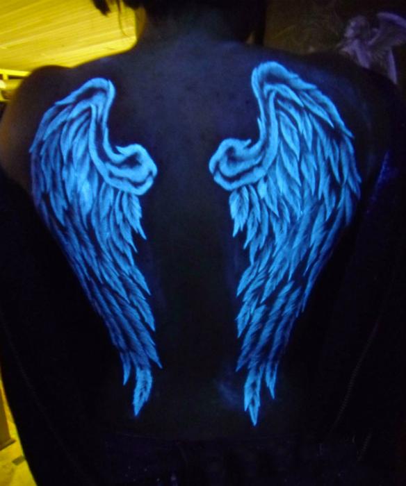 Флуоресцентная татуировка с изображением крыльев.